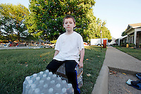 Ricky Guilmette, 7, of Nashville, sits on cases of water donated to residents and volunteers by Lowe's in the Nashville suburb of Bellevue on Saturday, May 8, 2010.