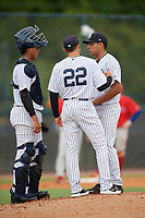 GCL Yankees East pitching coach Justin Pope (22) talks with pitcher Deivi Diaz (19) and catcher Hemmanuel Rosario (7) during a Gulf Coast League game against the GCL Phillies West on July 26, 2019 at the New York Yankees Minor League Complex in Tampa, Florida.  (Mike Janes/Four Seam Images)