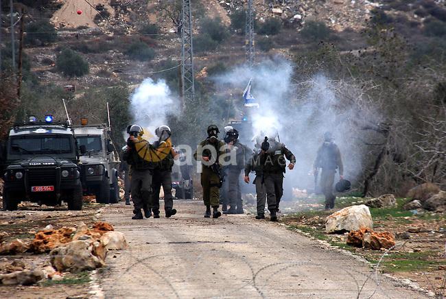 Israeli border police officers fire tear gas toward Palestinian demonstrators, who are seeking access to their land near Kufr Qaddum, near the northern West Bank Jewish settlement of Kdumim, Friday, Nov. 18, 2011. Photo by Wagdi Eshtayah