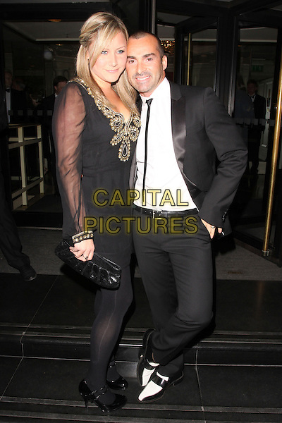 GUEST & LOUIE SPENCE .At the Sony Radio Academy Awards, Grosvenor House Hotel, Park Lane, London, England, UK, May 10th 2010..full length black suit tie white shirt hand in pocket shoes .CAP/AH.©Adam Houghton/Capital Pictures.