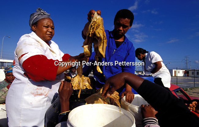 ditown00181 Digital. Township  Unidentified people selling cow intestines from a pick up truck on July 27, 2001 in Site B Khayelitsha, a township about 35 kilometers outside Cape Town, South Africa. It's popular for making traditional food. Khayelitsha is one of the poorest and fastest growing townships in South Africa. People usually come from the rural areas in Eastern Cape province to find work as maids and laborers. Most people don't find work and the unemployment rate is very high, together with lot of violence and a growing HIV-Aids epidemic itÕs a harsh area to live in. Vendor.©Per-Anders Pettersson/ iAfrika Photos.