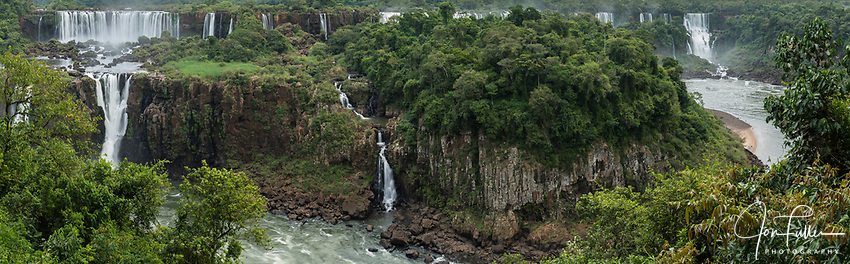 Iguazu Falls National Park in Argentina, as viewed from Brazil.  A UNESCO World Heritage Site.  Pictured  Rivadavia Falls at top left with one of the Three Musketeers Falls or Salto Tres Mosqueteros below.  The smaller lower falls at right is unnamed.  In the distance at right is Bossetti Falls.  Isla San Martin is in the center.