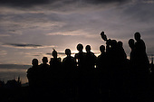 Lolgorian, Kenya. Siria Maasai Manyatta; group of moran, one with horn musical instrument, silhouette in evening light.