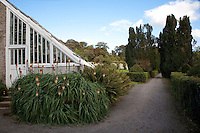 The angular glass roof of the peach house heralds the entrance to the kitchen garden