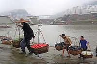 Porters known as stick men carry baskets of vegetables  banks of the Three Gorges Dam reservoir outside Fengie, China. Several of the new cities are suffering from structural damage due to land and earth movements caused by the 400 km Three Gorges reservoir..27 May 2010