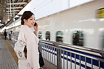 A kimono-clad woman stands on the platform waiting for a shinkansen bullet train in Yokohama, Japan on 03 Feb. 2012. Photographer: Robert Gilhooly