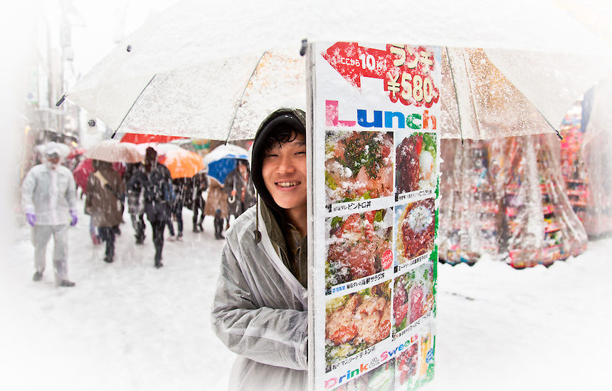 Young lad shelters and shivers behind his Lunch advertising board during rare heavy snow in Tokyo.