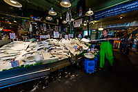 Tourists crowd around to watch fish being thrown (after they are purchased they are thrown to the counter to be weighed) at the Pike Place Fish Company, Pike Place Market, Seattle, Washington USA.