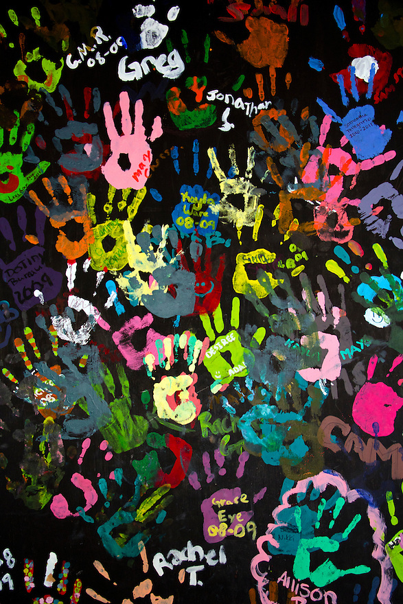 Children's colorful hand prints on black background for texture and design