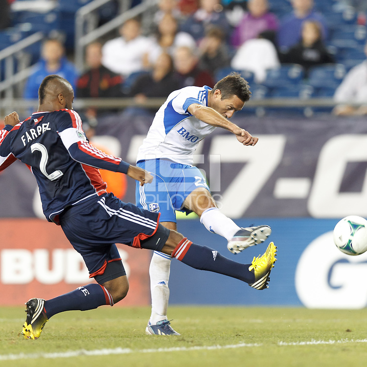 Montreal Impact midfielder Davy Arnaud (22) takes a shot as New England Revolution defender Andrew Farrell (2) defends. In a Major League Soccer (MLS) match, Montreal Impact (white/blue) defeated the New England Revolution (dark blue), 4-2, at Gillette Stadium on September 8, 2013.