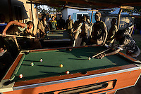 TANZANIA Geita, artisanal gold mining in Mgusu, where about 4000 people live and work, young miner play billiards after work  / TANSANIA Geita, kleine Goldminen in Mgusu, hier arbeiten und leben ca. 4000 Menschen, junge Bergleute spielen Billard nach der Arbeit
