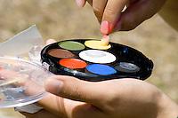 Artist dabs paint from pallet. Dragon Festival Lake Phalen Park St Paul Minnesota USA