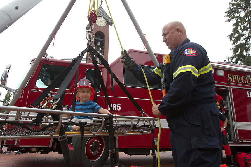 """Fire-fighter Bill Dunlap hoists Jonah Vandervoort 2  up in a rescue apparatus at """"Fire in the Park""""  in Vancouver Saturday July 16, 2016. Fire in the Park is the annual informational and charitable event hosted in Esther Short Park by the Vancouver Firefighters Union. It's a day of fire-safety and first-aid education for children and families — as well as fundraising for the victims of the real emergencies that firefighters respond to every day. (Photo by Natalie Behring/ for the The Columbian)"""