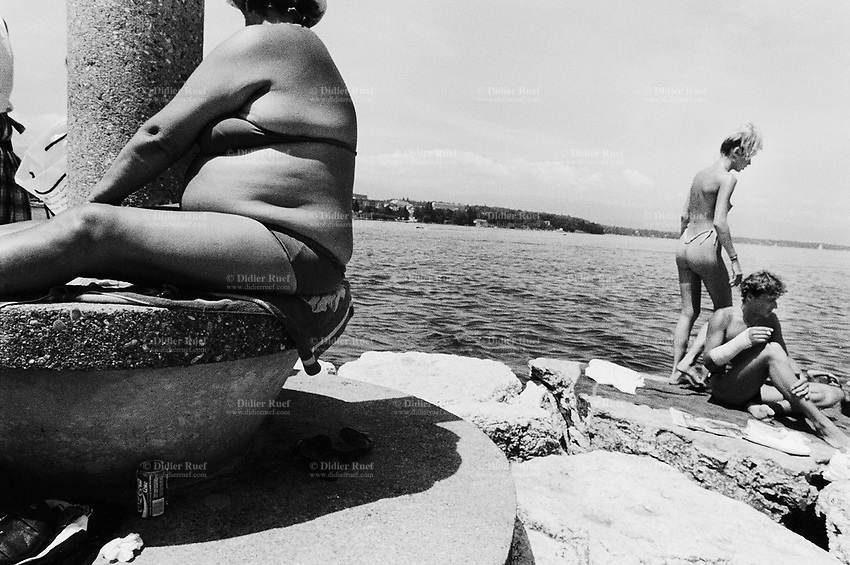 Switzerland. Geneva. Summer on the lake Geneva. A fat woman seats on a concrete platform close to a column. A couple enjoys sunbathing on the rocks. The pretty young woman stands up, wears a string and is topless. The man is seated, smokes a cigarette and has one's fore arm in plaster. © 1987 Didier Ruef