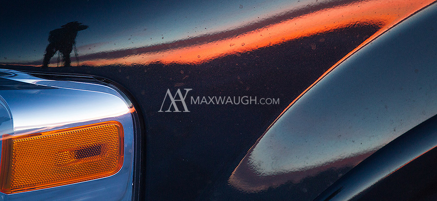 A photographer is reflected on the hood of a car during a sunset shoot in Yellowstone.