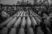 People pray behind coffins of Muslim men killed 27 years ago by Bosnian Serb forces, during a mass funeral for the victims in Kozarac July 20, 2019.
