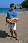 A food vendor offering baked goods makes the rounds at Olimpos Beach on Turkey's Mediterraneian coast.