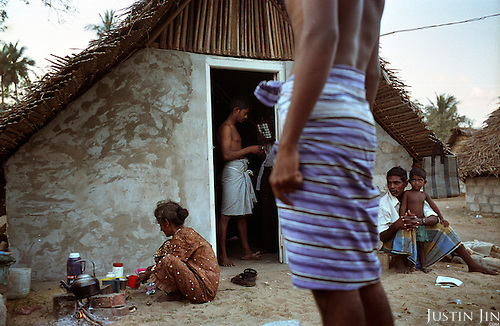 A family gets ready for breakfast outside its refugee hut in Mullaitivu, on the northeastern coast of Sri Lanka, an area ravaged also by civil war. .The December 26, 2004 tsunami killed around 40,000 people along Sri Lanka's southern, eastern and northern shores, tearing thousands of families apart. .The bulk of the dead were women and children - husbands lost young brides and around 4,000 children lost one or both parents. .Even before the tsunami struck, people here in the northeast had already been displaced four times by the Tigers' two-decade war for autonomy. .In some places, the scars of war and the tsunami have become one. Remnants of walls torn down by waves are pockmarked with bullet holes and shrapnel from shells fired before a 2002 ceasefire plunged a civil war that killed over 64,000 people into limbo. ..Picture taken March 2005 by Justin Jin