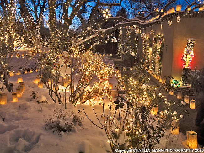 Paper bag faralitos and  lights strung in the trees adorn a Canyon Road home during the annual Christmas Eve celebration in Santa Fe, New Mexico