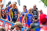 24 JUN 2012 - KITZBUEHEL, AUT - Competitors, including Alistair Brownlee (GBR) of Great Britain (centre, in blue and white), wait for the start of the elite men's 2012 World Triathlon Series round in Schwarzsee, Kitzbuehel, Austria (PHOTO (C) 2012 NIGEL FARROW)