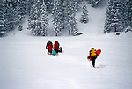 Families crossing snow-covered lake heading toward sledding area, Rocky Mtns, CO