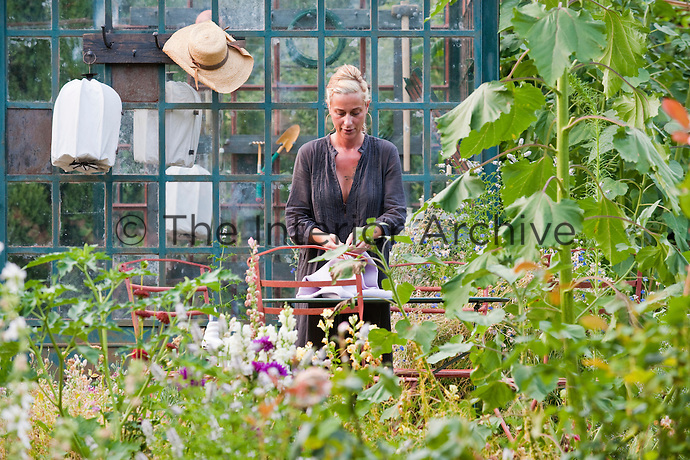 Maddalena Caruso in her herb garden laying a tablecloth for an al fresco dinner