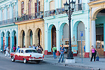Havana, Cuba; a red and white 1956 Ford Fairlane parked in front of pastel colored buildings, along Paseo de Marti, in early morning soft light