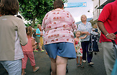 An obese woman walks in the street in the small Languedoc town of St Jean du Gard