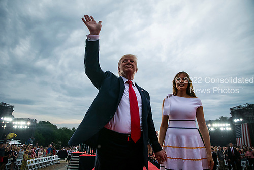 """U.S. President Donald Trump waves with first lady Melania Trump during the Fourth of July Celebration 'Salute to America' event in Washington, D.C., U.S., on Thursday, July 4, 2019. The White House said Trump's message won't be political -- Trump is calling the speech a """"Salute to America"""" -- but it comes as the 2020 campaign is heating up. <br /> Credit: Al Drago / Pool via CNP"""