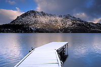 Snow covered dock in winter on Fallen Leaf Lake below mountains, near Lake Tahoe, Sierra Nevada, California.