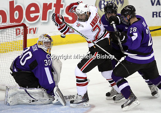 UNO's Matt Ambroz and Minnesota State University-Mankato goalie Phil Cook track the puck as it sails through the crease. (Photo by Michelle Bishop)