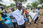 Using a megaphone, a man leads a group of refugees in song during an activity sponsored by Jesuit Refugee Service in the Doro Refugee Camp in Maban, South Sudan. The camp is one of four in Maban that together shelter more than 130,000 refugees from the Blue Nile region of Sudan.<br /> <br /> Misean Cara supports the work of JRS in the Maban camps.