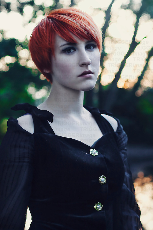 Young girl with short orange hair and pale skin, wearing a black velvet dress, looking with a sad expression at the camera, with forest background.