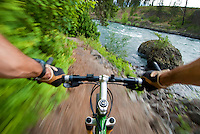 POV, Point of View shot over handlebars of speeding mountain biker, Centennial Trail Spokane River, Spokane WA.