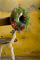 A Christmas wreath made with moss and winter berries hanging on the side of a garden bench