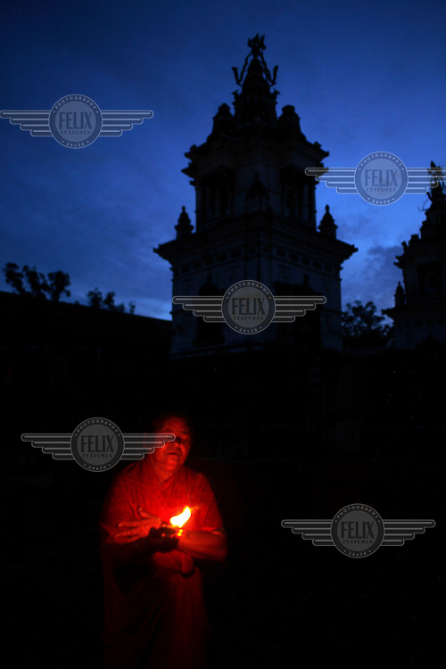 An elderly resident lights a candle after dark in the Pashupati Bridhashram (old peoples' home). Part of the Pashupatinath Temple complex, the old peoples' home is the largest of its type in Kathmandu, home to 140 women and 90 men. Nepal has a steadily growing elderly population.