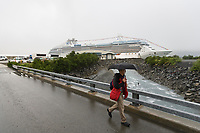 """Tourist walks along the rainy road in Whittier, Princess Cruise liner """"Island Princess"""" docked nearby."""