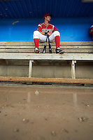 Batavia Muckdogs catcher Blake Anderson (26) sits on top of the bench as the dugout floods during a game against the Mahoning Valley Scrappers on July 1, 2015 at Dwyer Stadium in Batavia, New York.  The game was called after four pitches because of rain.  (Mike Janes/Four Seam Images)