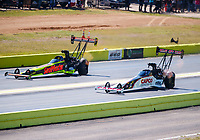 Oct 15, 2017; Ennis, TX, USA; NHRA top fuel driver Steve Torrence (right) races alongside Richie Crampton prior to blowing a tire and crashing his dragster as he wins in the second round of the Fall Nationals at the Texas Motorplex. Torrence walked away from the crash. Mandatory Credit: Mark J. Rebilas-USA TODAY Sports