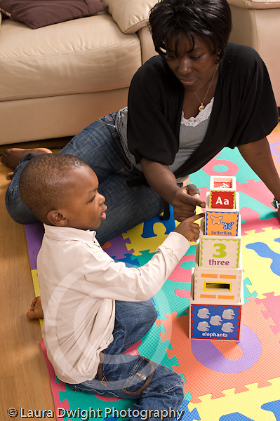 2 year old toddler boy with mother interaction playing with toys language development mother talking and involved  counting or pointing at picture on blocks African American vertical