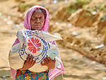 A Rohingya woman carries home a bag of food provided by Caritas in the Mainerghona Refugee Camp near Cox's Bazar, Bangladesh, on October 27, 2017. She is among the more than 600,000 Rohingya who since August have fled government-sanctioned violence in Myanmar for safety in Bangladesh.