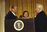 Chief Justice Warren Burger administering the Oath of Office to President Gerald R. Ford while Betty Ford looks on. 9 August 1974