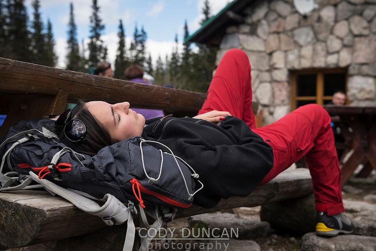 Female hiker sleeps on bench outside Murowaniec hut, Tatra mountains, Poland