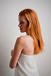 Young red haired woman wrapped in a towel, side view