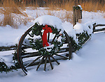 Bureau County, IL <br /> Holiday decorations and fresh snow on a wagon wheel and split rail fence.  Tall grass prairie and winter forest in the background.