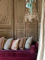 A detail of a traditional sitting room with painted walls. A row of cushions are placed on a red sofa.