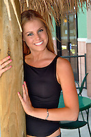 A teenage girl with a big smile and blonde hair wearing a black top, leans holds a wooden pillar