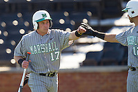 Aaron Bossi (17) of the Marshall Thundering Herd bumps fists with teammate Eric Escobedo (12) after scoring a run against the Georgetown Hoyas at Wake Forest Baseball Park on February 15, 2014 in Winston-Salem, North Carolina.  The Thundering Herd defeated the Hoyas 5-1.  (Brian Westerholt/Four Seam Images)