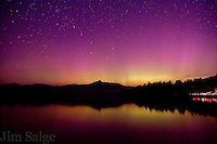 The Northern Lights make an appearance over Chocorua Lake and Mount Chocorua in New Hampshire. A car drives up Route 16 along the lakeshore, likely unaware of the solar storm overhead.