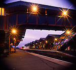 Train heading towards platform on an empty train station at dusk..England, Uk